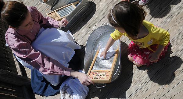 Sarah Owens (left) teaches Sloan Turnbow how to use a washboard during the Cherokee Strip Regional Heritage Center Family Fun Day in Humphrey Heritage Village Saturday, April 13, 2013. (Staff Photo by BONNIE VCULEK)