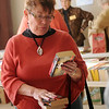 Ann Ritchie, a former Enid Public Schools English teacher, selects her purchases at the Hospice Circle of Love spring book sale Friday, April 12, 2013. Avid readers support the annual event because the fundraiser benefits Hospice clients. (Staff Photo by BONNIE VCULEK)