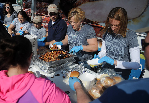 Roberts Ranch employees serve pulled pork sandwiches during the 8th annual Roberts Ranch Smokin' Red Dirt BBQ outside Convention Hall Friday, April 19, 2013. (Staff Photo by BONNIE VCULEK)