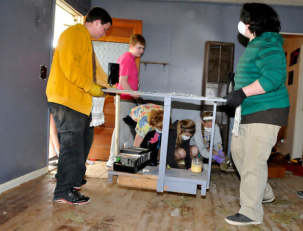 Youths from Central Christian Church and the First Christian Church of Sulphur help to remove items of house on north 5th street that is being remodeled by Forgotten Ministries. (Staff Photo by BILLY HEFTON)