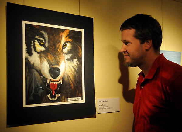 """Dave Kennedy, Curator of Collections at the Cherokee Strip Regional Heritage Center, examines """"The Alpha Male"""" entry by Kayla Riddle, from Seiling Senior High School Tuesday, April 16, 2013. """"The Alpha Male"""" was selected as the Harold T. Holden award winner during the Pioneer Cellular Smokin' Red Dirt Arts Festival. A reception honoring the top three winners in Divisions I-III was held at the Cherokee Strip Regional Heritage Center Tuesday evening. Student categories included oil, acrylic, charcoal or graphite drawing, watercolor, mixed media, sculpture/3D and photography. (Staff Photo by BONNIE VCULEK)"""