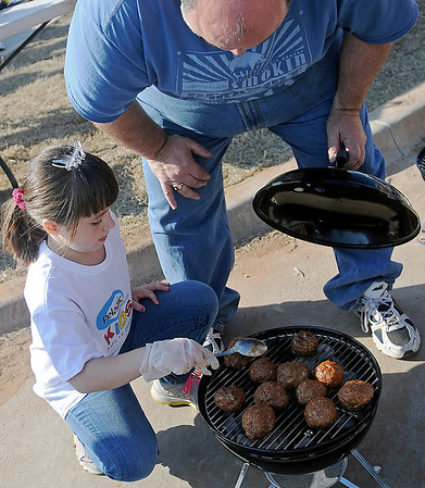 As Grandpa Brad Nulph watches, Madison Nulph (left) turns the Greybeard Babies' gourmet meatballs during the 1st annual Pelagic Tank Kids Q at the 8th annual Roberts Ranch Smokin' Red Dirt Barbeque Friday, April 19, 2013. (Staff Photo by BONNIE VCULEK)