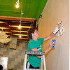 Bryan Becker of the 1st Christian Church of Midwest City scrubs the walls at Five 80 Coffee Shop Saturday. Central Christian Church is hosting youths from around the state as they work on mission projects. (Staff Photo by BILLY HEFTON)
