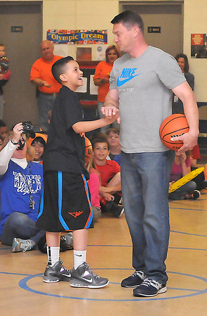 Taurion Sullivan shakes hands with Brent Price Wednesday at Taft Elementary during a send off assembly. Sullivan is headed to Springfield, MA to compete in a national free throw shooting contest. (Staff Photo by BILLY HEFTON)