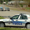 An Enid patrol car sits along 54th street Monday as units from the Enid Police department, Garfield County Sheriff's department and the Oklahoma Highway Patrol search for a suspect. (Staff Photo by BILLY HEFTON)