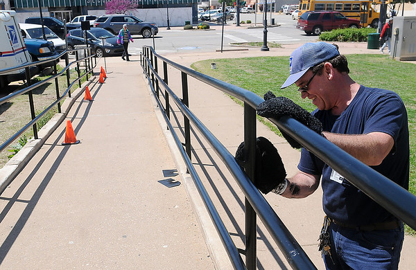 United States Postal Service maintenance employee Christopher Grellner uses mitts to paint the handicap rails outside the Enid post office as a woman arrives to pick up her mail Wednesday, April 24, 2013. (Staff Photo by BONNIE VCULEK)