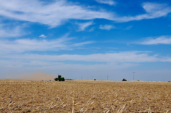 Dust billows up from behind a tractor as a farmer prepares a field for planting north of Carrier Saturday. (Staff Photo by BILLY HEFTON)