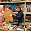 Jean Syoen and Cathy Wiles lift a box of donated items as they prepare for the Hospice Circle of Love book sale to be held April 4 & 5. (Staff Photo by BILLY HEFTON)