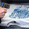 Cheryl Cooksey, the graphic arts instructor at Autry Technology Center, checks the temperature of a screen print at Privation Printing Thursday, April 17, 2014. Students in graphic arts classes at Autry Technology Center created shirt designs and learned the screen print process from Timothy Larsen, owner of Privation Printing, an incubator company in the James W. Strate Center for Business Development at 2020 Willow Run Street. (Staff Photo by BONNIE VCULEK)