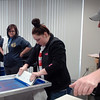 Graphic Arts students (left) wait patiently as Haley Blewitt (center), from Timberlake High School, screen prints a t-shirt at Privation Printing Thursday, April 17, 2014. Students in Cheryl Cooksey's graphic arts classes at Autry Technology Center created shirt designs and learned the screen print process from Timothy Larsen (right), owner of Privation Printing, an incubator company in the James W. Strate Center for Business Development at 2020 Willow Run Street. (Staff Photo by BONNIE VCULEK)