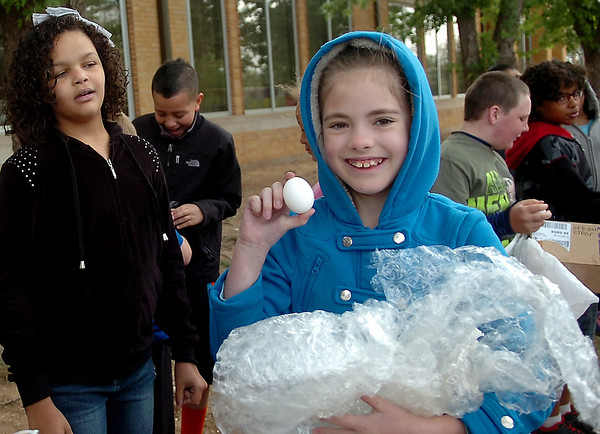 Nevaeh Prock holds her uncracked, raw egg after her recycled container protected its cargo during the 4th grade egg drop competition at Taft Elementary School Tuesday, April 29, 2014. (Staff Photo by BONNIE VCULEK)