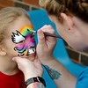 Jo DeLorenzi completes a facial design for her daughter Lillian during the Kermesse Festival at St. Joseph Catholic School Saturday, April 26, 2014. (Staff Photo by BONNIE VCULEK)