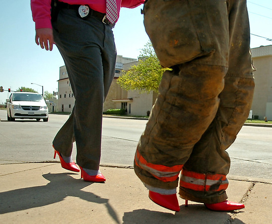 "An Enid police officer and firefighter sport red high heels as they strut past traffic on Owen K. Garriott during the YWCA ""Walk a Mile in Her Shoes"" Tuesday, April 22, 2014. More than 70 men participated in the fundraising event for the YWCA. (Staff Photo by BONNIE VCULEK)"