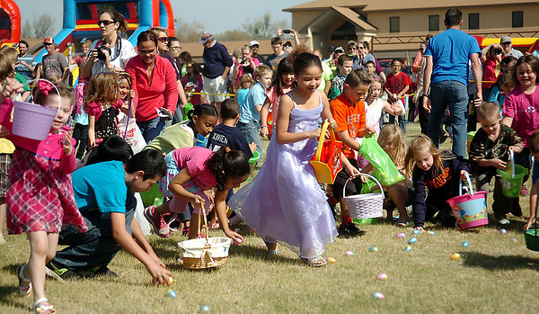Children snatch candy-filled eggs off the Oakwood Christian Church lawn during Easter Eggstravaganza Saturday, April 19, 2014. A total of 20,000 eggs for the six egg hunts, inflatables, food and games were prepared for the community event. (Staff Photo by BONNIE VCULEK)