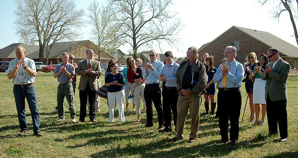 Individuals applaud during the groundbreaking ceremony at Chisholm Creek Village Tuesday, April 22, 2014. David Ritchie (far left) plans to build 30 new geothermal Energy Star homes within the next two years as part of the economic development in Enid. (Staff Photo by BONNIE VCULEK)