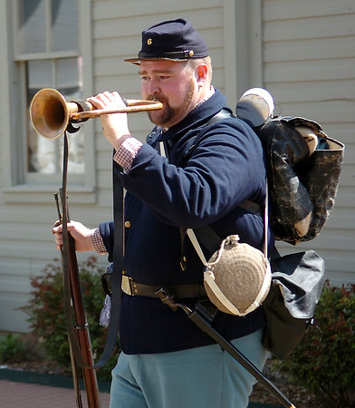 Cody Jolliff, education director at the Cherokee Strip Regional Heritage Center, sounds a bugle during a Civil War demonstration for St. Mary's Episcopal School students from Edmond at Humphrey Heritage Village Wednesday, April 23, 2014. (Staff Photo by BONNIE VCULEK)