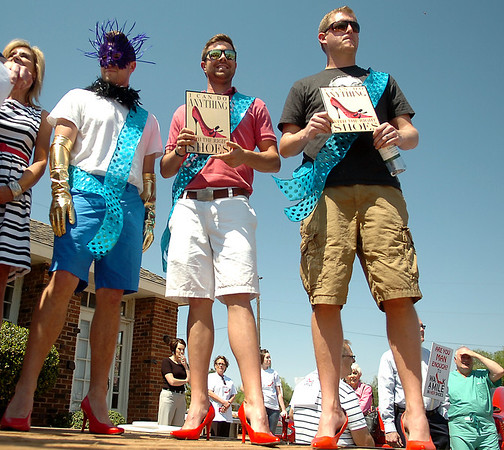 """Don Snyder, Jonathon Epps and Matt Anderson (from left) don bright red high heels during the YWCA Walk A Mile in Her Shoes fundraising event Tuesday, April 22, 2014. The three were honored as the best dancer, best legs and best stride respectively. More than 70 men were """"man enough"""" for the high heel walk from the YMCA to RSVP. (Staff Photo by BONNIE VCULEK)"""