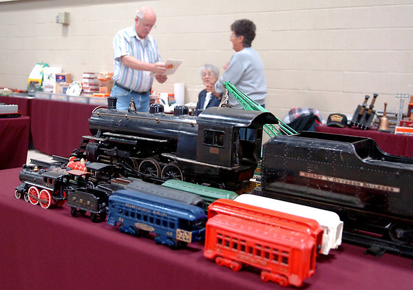 Antique model and toy trains are displayed as Elmer Sheely (left) and his wife, Santiaga (center), visit with another train enthusiast during the Cherokee Strip Model Railroad Association Railfest at the Chisholm Trail Expo Center Pavilion Saturday, April 19, 2014. (Staff Photo by BONNIE VCULEK)