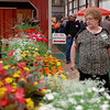 Jane Howell glances at the Garden House's beautiful floral display during the 39th annual Enid Home Show Saturday, April 26, 2014. (Staff Photo by BONNIE VCULEK)