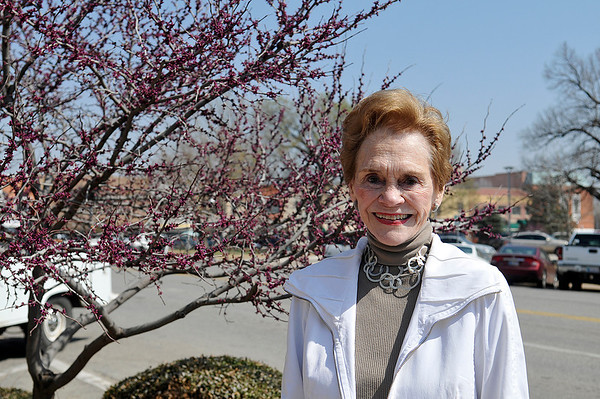 Suzy Miebergen stands by a redbud tree in downtown Enid. (Staff Photo by BILLY HEFTON)