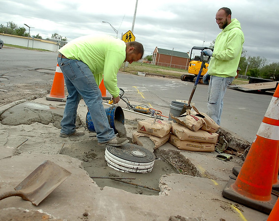 Steve Cowherd (left) and Andrew Perry, form Northwest Plumbing & Mechanical Inc., mix and pour concrete by hand after repairing a plumbing leak at Food Mart on the corner of Grand and Willow Tuesday, April 29, 2014. (Staff Photo by BONNIE VCULEK)