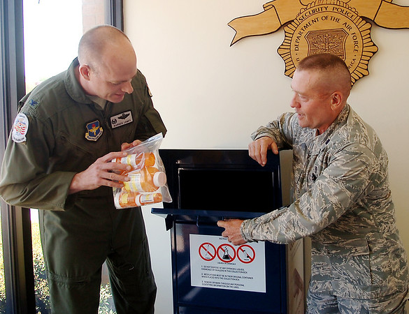 Col. Darren James (left), Commander of the 71st Flying Training Wing, and Lt. Col. Royce Terry place a bag of unused prescription drugs into the new drug drop box in the Vance Air Force Base 71st Security Forces Squadron building Friday, April 25, 2014. The new drop box was provided by PreventionWorkz. (Staff Photo by BONNIE VCULEK)
