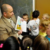 Representative John Enns shows the book illustrations to students at the Westside Head Start Center Friday. (Staff Photo by BILLY HEFTON)