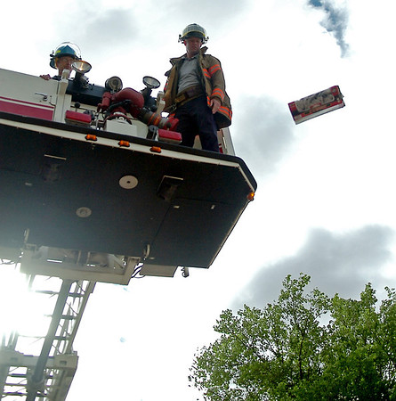 Enid Fire Department Assistant Mechanic John Buller (left) and Firefighter Mike Schatz drop the final raw egg container from the aerial platform during the 4th grade egg drop competition at Taft Elementary School Tuesday, April  29, 2014. (Staff Photo by BONNIE VCULEK)