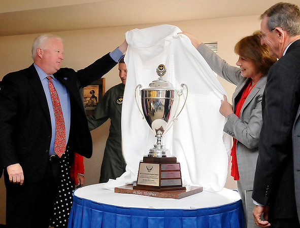 Dr. Joe Leverett (left), chairman of the Altus Military Affairs Comminttee and Andi Holland unveil the Altus Award Trophy during a ceremony Wednesday at Woodring Airport. (Staff Photo by BILLY HEFTON)