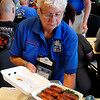 Table captain, Lorraine Hilton from Rhode Island, presents a box of chicken to be judged at the Red Dirt Barbeque contest Saturday. (Staff Photo by BILLY HEFTON)