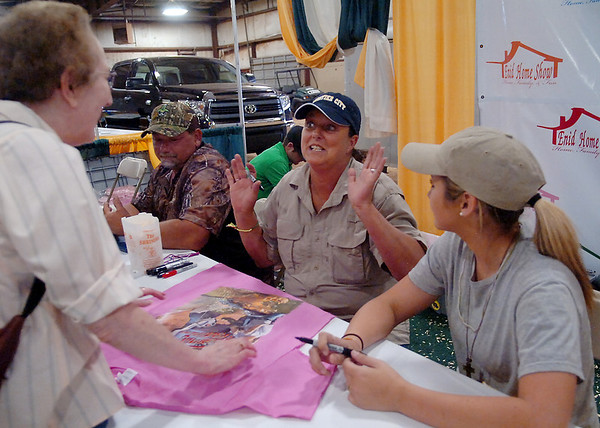 """Gator Queen Liz Choate shares a special moment with a fan during the 39th annual Enid Home Show at the Chisholm Trail Expo Center Friday, April 25, 2014. Justin Choate, Gator Queen Liz and Snagger Jessica Cavalier (seated from left) will again be featured on the History Channel's show """"Swamp People."""" (Staff Photo by BONNIE VCULEK)"""