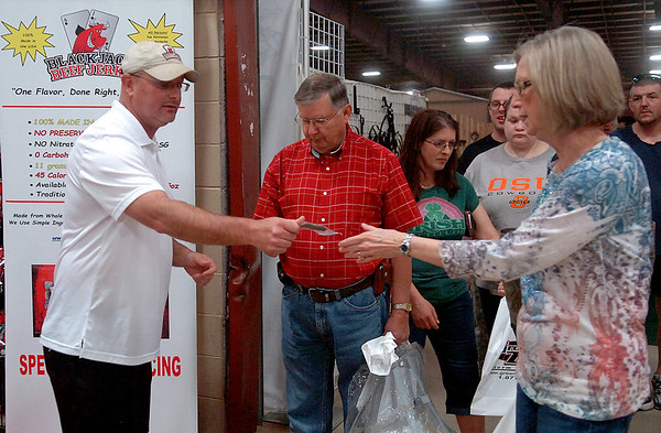 Jeff Smith, with Blackjack Beef Jerky, passes out free samples to Enid Home Show visitors at the Chisholm Trail Expo Center Saturday, April 26, 2014. (Staff Photo by BONNIE VCULEK)