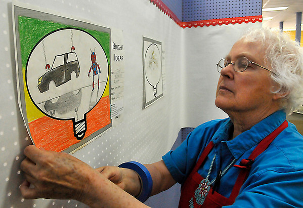 Margaret Moss hangs the Best in Show drawing, The Working Robot, by Jolina Kejlat from Longfellow Middle School Monday. (Staff Photo by BILLY HEFTON)