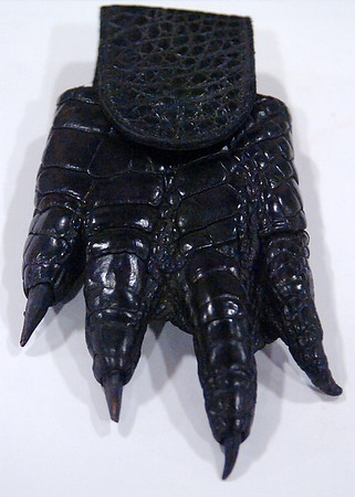 """A large cell phone case made from an alligator's foot is part of a silent auction by Gator Queen Liz Choate and Snagger Jessica Cavalier at the 39th annual Enid Home Show. Proceeds from the auction will go to St. Jude's Children's Hospital. Choate and Cavalier star in the History Channel show, """"Swamp People."""" (Staff Photo by BONNIE VCULEK)"""
