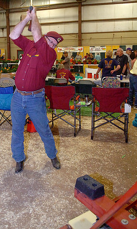 Enid Shriners' Larry Lewis keeps his eye on the target as he swings a giant hammer and rings the bell during the Enid Home Show Saturday, April 26, 2014. (Staff Photo by BONNIE VCULEK)