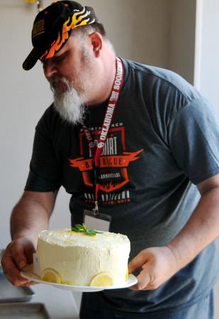 Robert Johnson delivers the Wild Oaks BBQ's dessert, a lemon cake Saturday, April 18, 2015. (Staff Photo by BONNIE VCULEK)