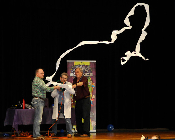 Chisholm Elementary teachers, Roy Bartwick (left) and Tim Braley, assist Mad Science's Derrick Brack during a performance at Chisholm Elementary Thursday April 14, 2016. (Billy Hefton / Enid News & Eagle)