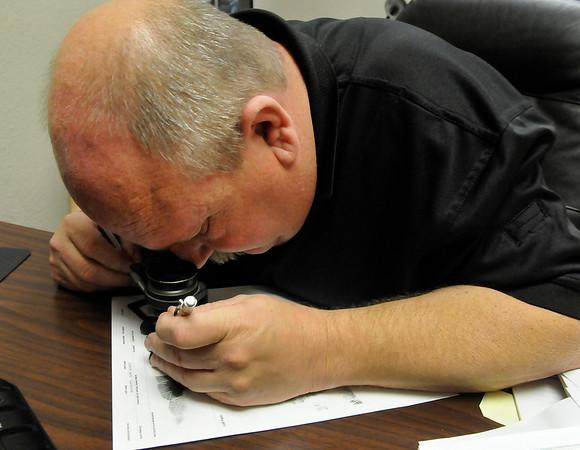 Tim Hess, Enid Police Department crime scene technician, analyzes fingerprints April 7, 2016. (Billy Hefton / Enid News & Eagle)