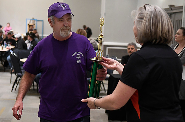 Buster Kirk receives the People's Choice first trophy from Donna Patocka during the awards ceremony for the 12th Smokin' Red Dirt BBQ Saturday April 22, 2017 at the Central National Bank Center. (Billy Hefton / Enid News & Eagle)