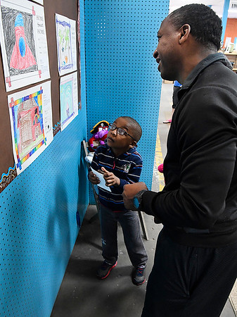 "Eisenhower Elementary first grader, Micaiah Redman, explanis his drawing to his dad, Covito Redmad, during the ""Home Sweet Home"" art show Saturday April 8, 2017 at Park Avenue Thrift. (Billy Hefton / Enid News & Eagle)"