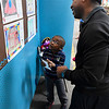"""Eisenhower Elementary first grader, Micaiah Redman, explanis his drawing to his dad, Covito Redmad, during the """"Home Sweet Home"""" art show Saturday April 8, 2017 at Park Avenue Thrift. (Billy Hefton / Enid News & Eagle)"""