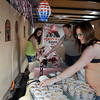 (left to right) Tori, Toni and Jenifer Daniels from Truckin Good BBQ sets up a trailer for the People's Choice competition during Smokin' Red Dirt BBQ contest Friday April 21, 2017 in downtown Enid. (Billy Hefton / Enid News & Eagle)