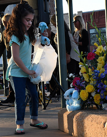 Zaelynn Thresher places stuffed animals next a bouquet of flowers during a memorial service for Enid's Baby Boy Angel Friday April 14, 2017 at the Garfield County Courthouse gazebo. (Billy Hefton / Enid News & Eagle)