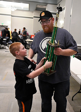 Travis Clark shares the Grand Champion trophy with his son, Cooper, during the awards ceremony for the 12th Smokin' Red Dirt BBQ Saturday April 22, 2017 at the Central National Bank Center. (Billy Hefton / Enid News & Eagle)