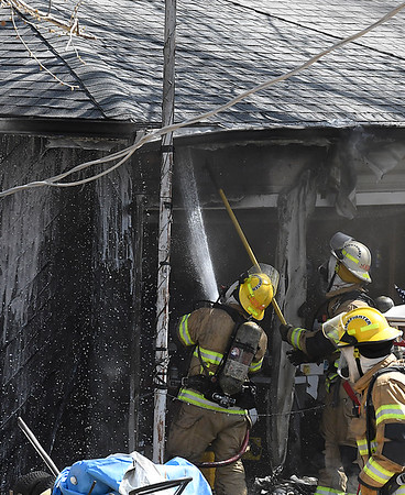 Enid firefighters work a house fire at 701 Windmeer Thursday April 19, 2018. (Billy Hefton / Enid News & Eagle)