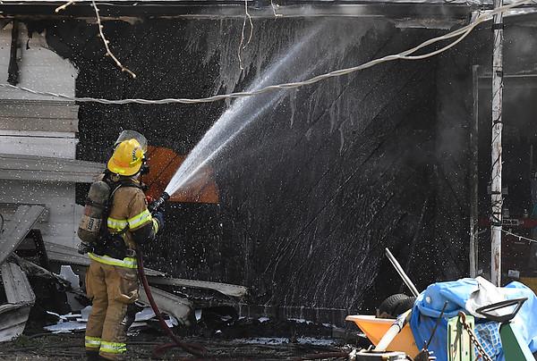 An Enid firefighter sprays a house at 701 Windmeer Thursday April 19, 2018. (Billy Hefton / Enid News & Eagle)