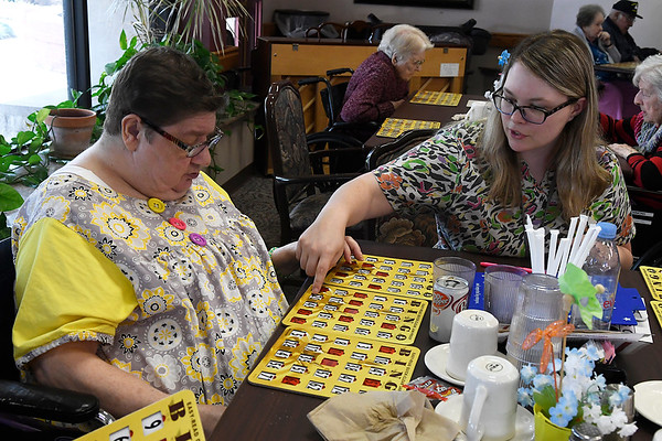 Leah Adkins, Commons Activities, assists Girtie Maner during a game of Bingo Monday April 30, 2018.(Billy Hefton / Enid News & Eagle)