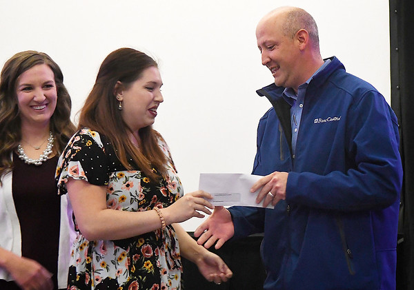 Jenny Grittman (left) and Natalie Beurlot, from the Junior Welfare League of Enid, present Todd Hamilton, of the Chisholn Foundation, with a check during a monthly meeting at the Stride Bank Center Monday April 1, 2019. (Billy Hefton / Enid News & Eagle)