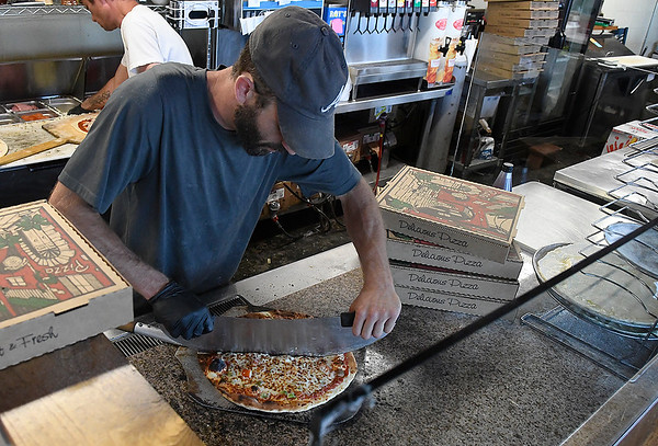 Colton Glasscock cuts a pizza at Brick Oven Pizza Wednesday, April 29, 2020. (Billy Hefton / Enid News & Eagle)