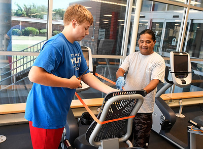 Nick Boeckman (left) and Laji Juadik place orange tape on a recumbent stationary bike at the Denny Price Family YMCA Thursday, April 30, 2020 to ensure social distancing. The YMCA is planning to open by appointment Monday, May 4. (Billy Hefton / Enid News & Eagle)